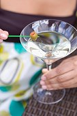 Woman holding green olive on cocktail stick over Martini glass