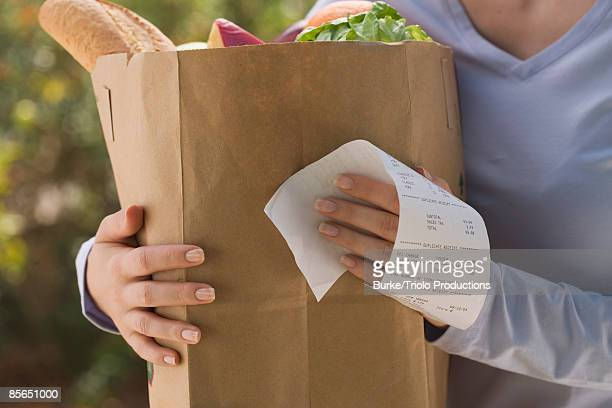 Woman holding grocery bag and receipt
