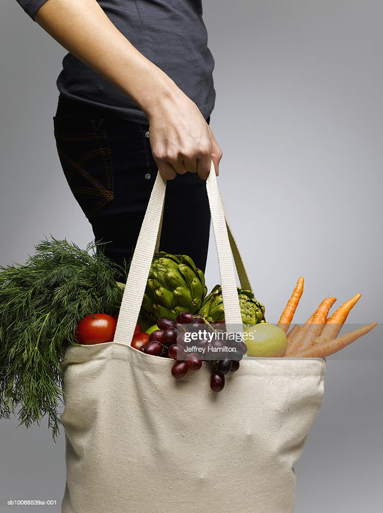 Woman holding grocery bags containing vegetables, mid section : Stock Photo