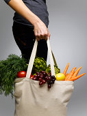 Woman holding grocery bags containing vegetables, mid section