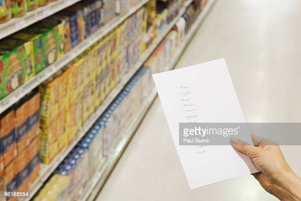 Woman Holding Grocery List in Grocery Store
