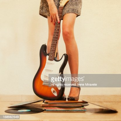 Woman holding guitar and standing on books. : Stock Photo
