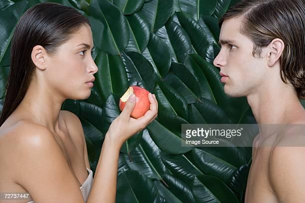 Femme tenant la moitié mange une pomme en face de l'homme