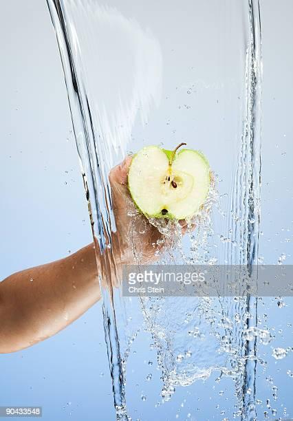 Woman holding halfa green apple in a waterfall