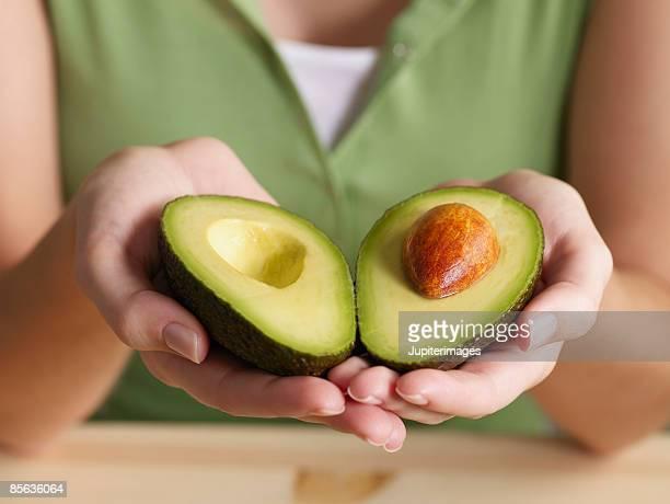Woman holding halved avocado