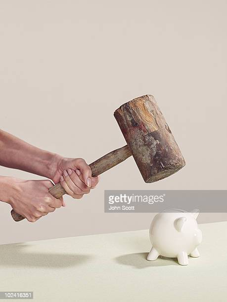 Woman holding hammer over a piggy bank