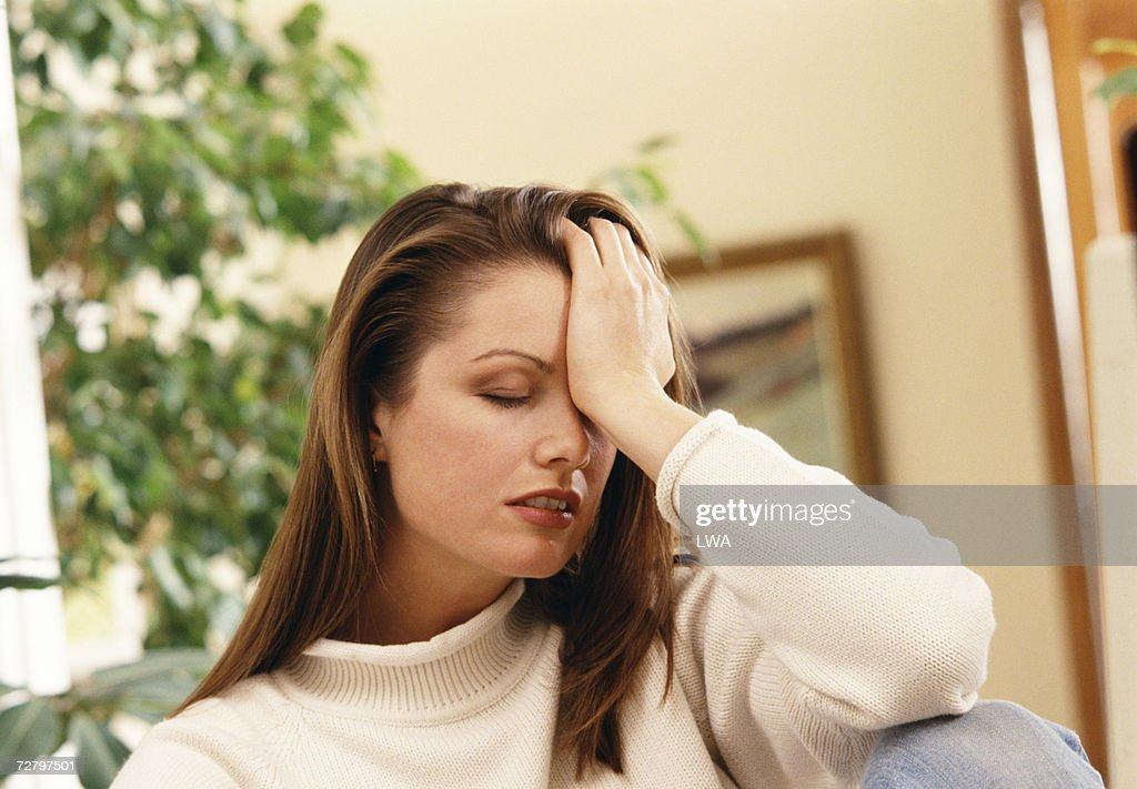 Woman Holding Hand Against Forehead Indoors Stock Photo ...