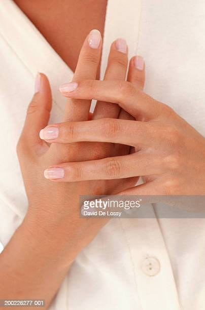 Woman holding hand close to chest