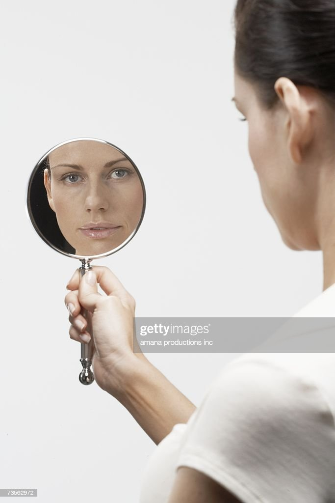 woman holding hand mirror. woman holding hand mirror : stock photo o