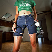 Woman holding hand mixer, tee-shirt says just say no mid-section