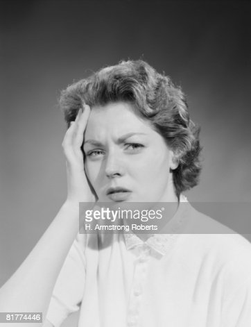 Woman Holding Hand To Forehead With Pained Expression ...