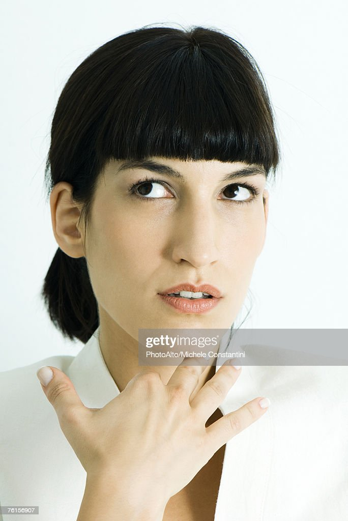 'Woman holding hand under chin, looking away, portrait'