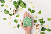 cropped shot of woman holding handcrafted soap on white surface
