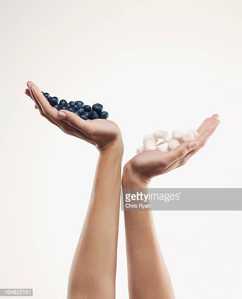 Woman holding handful of blueberries over handful of sugar cubes