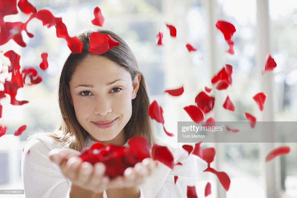 Woman holding handful of flower petals : Stock Photo
