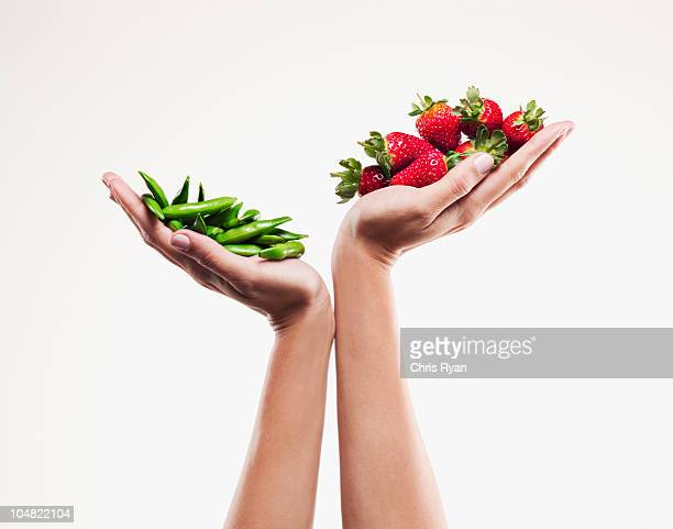 Woman holding handful of strawberries over handful of pea pods