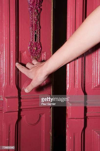 Woman holding handle of apartment door