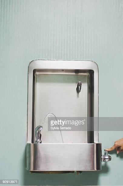 Woman holding handle of drinking fountain