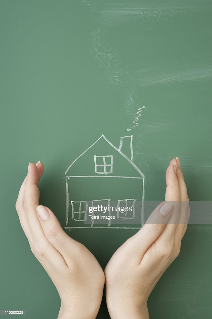 Woman holding hands around house drawn on blackboard