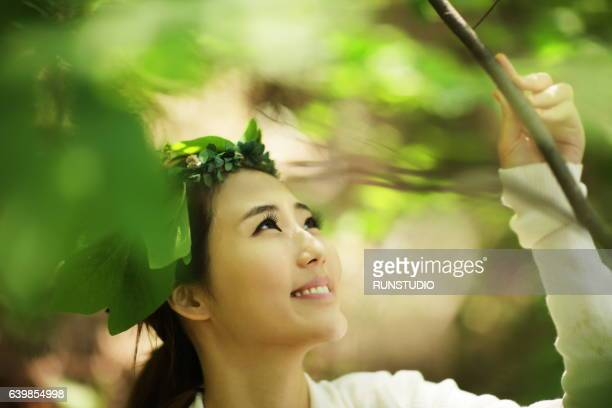 woman holding hands branches of trees