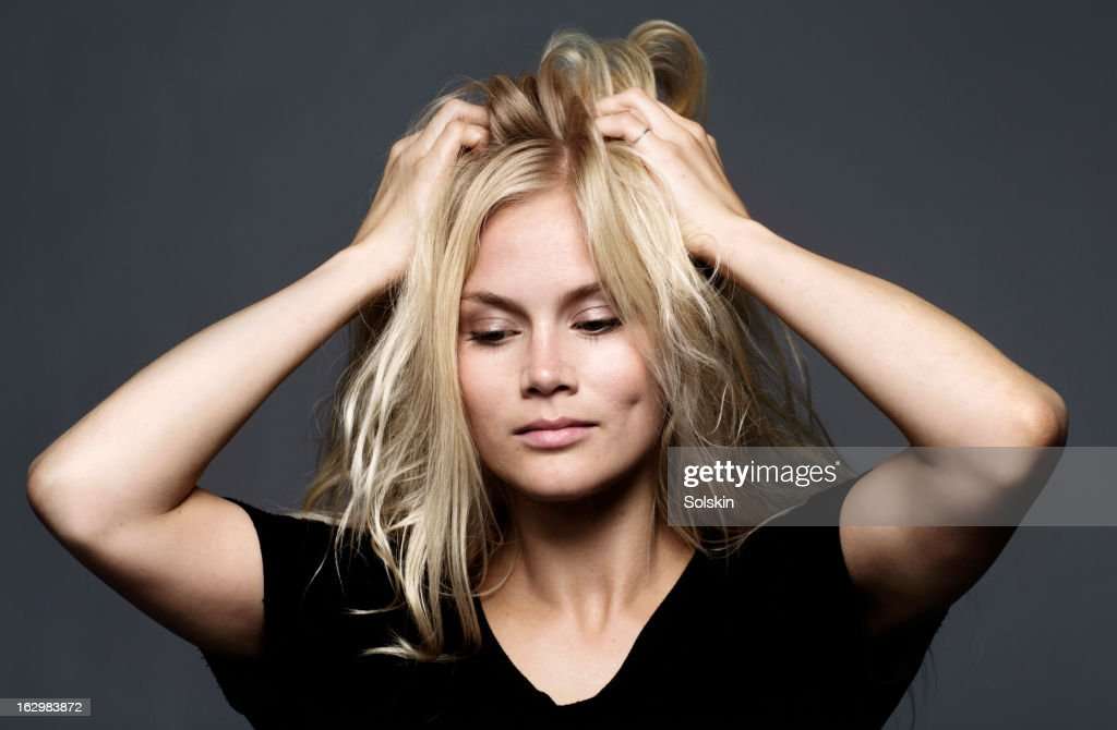 Woman holding hands to her hair, studio background : Stock Photo