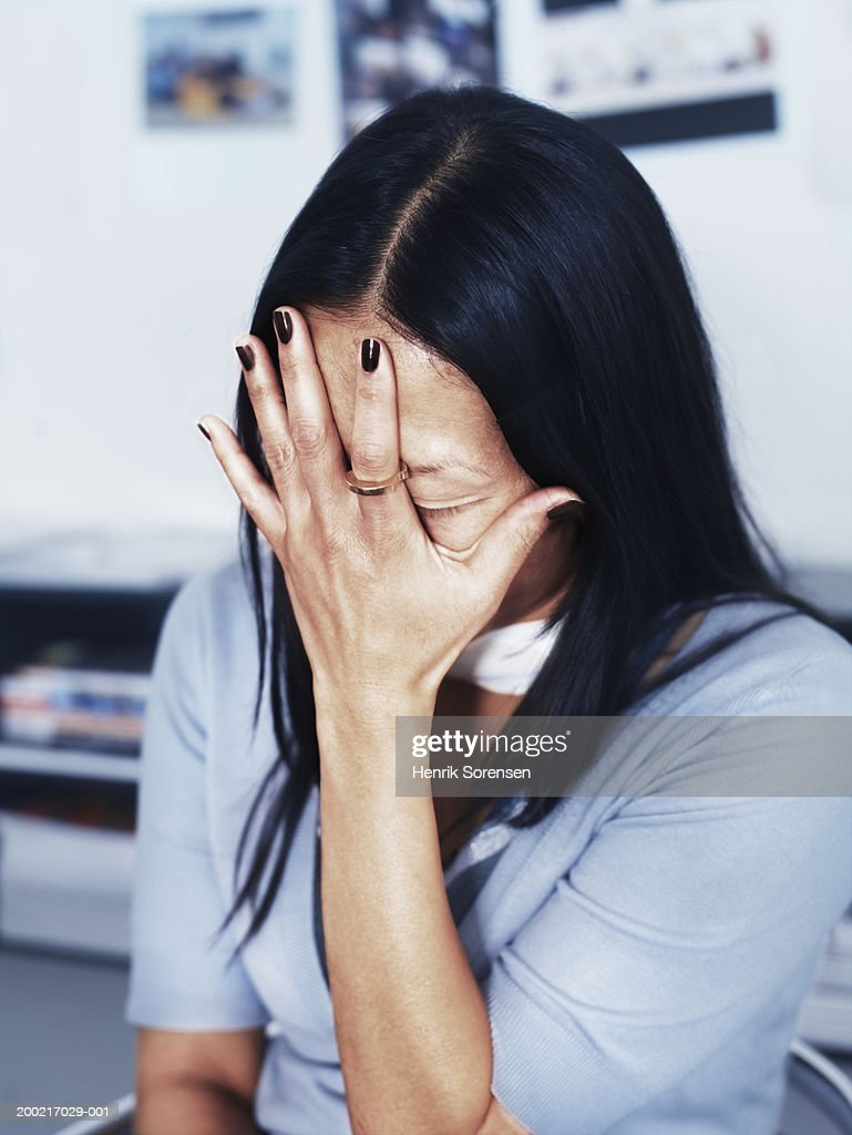 Woman holding head in hand, eyes closed, close-up : Stock Photo