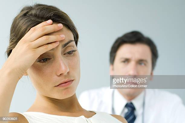 Woman holding head, looking down, doctor in background
