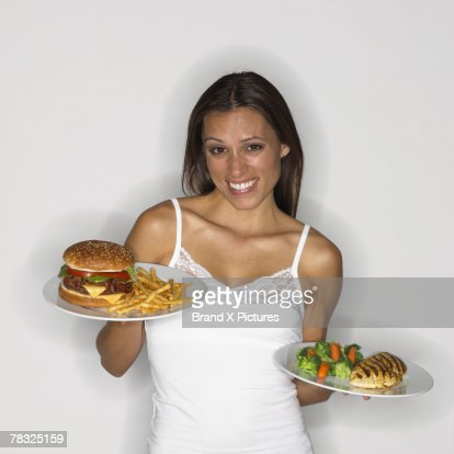 Woman holding healthy and unhealthy dishes : Stock Photo