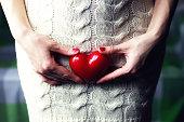 female hand holding a heart shape closeup