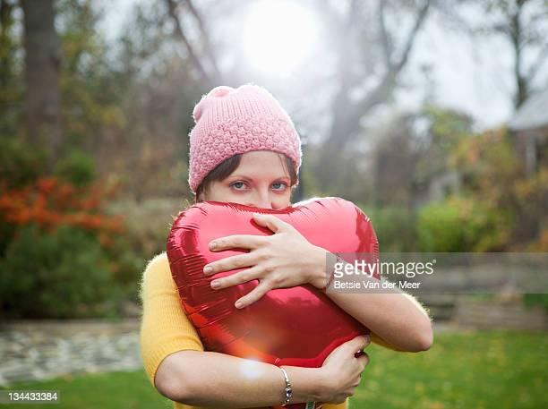 woman holding heart shape balloon in autumn light.