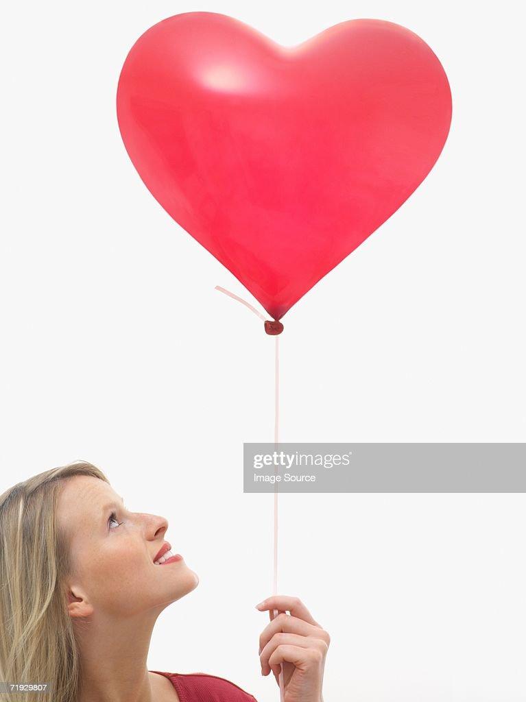 Woman holding heart shaped balloon : Stock Photo