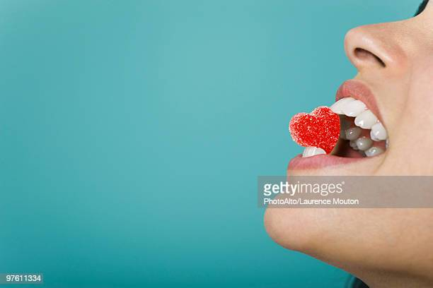 Woman holding heart-shaped candy between teeth, cropped