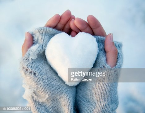 Woman holding heart-shaped snowball, close-up of hands