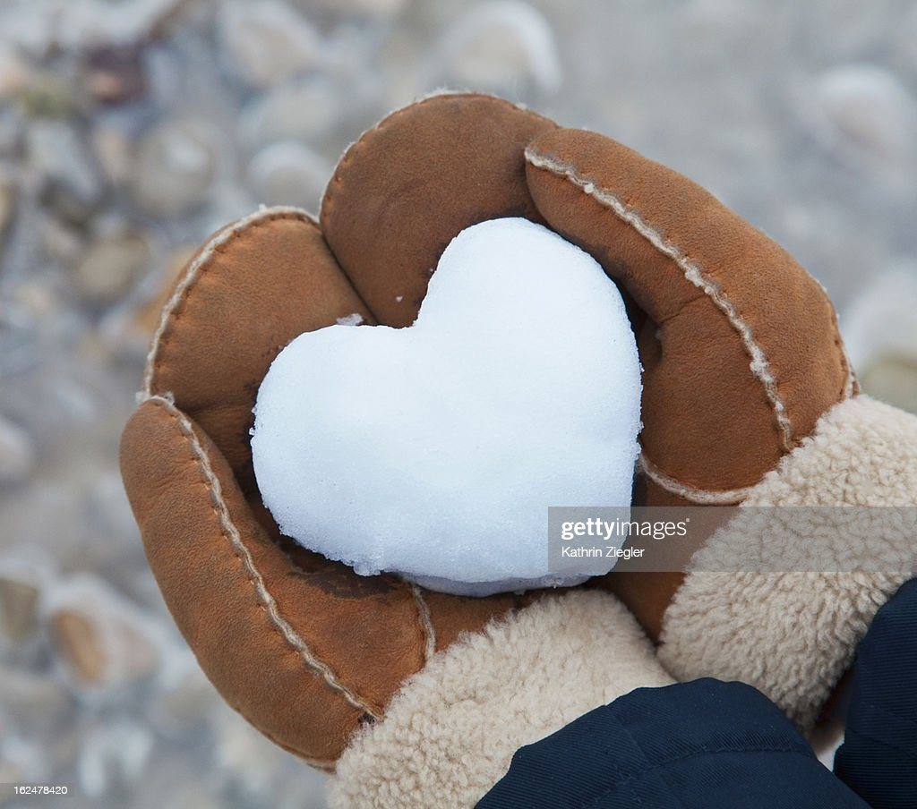 woman holding heart-shaped snowball, close-up : Stock Photo