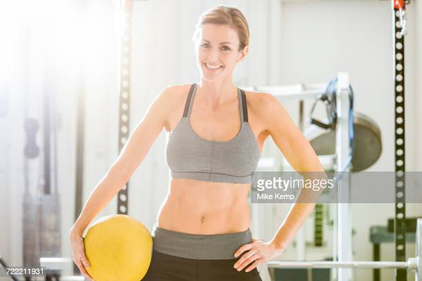 Woman holding heavy ball in gymnasium