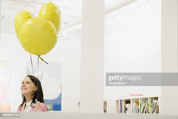 Woman holding helium balloons in office