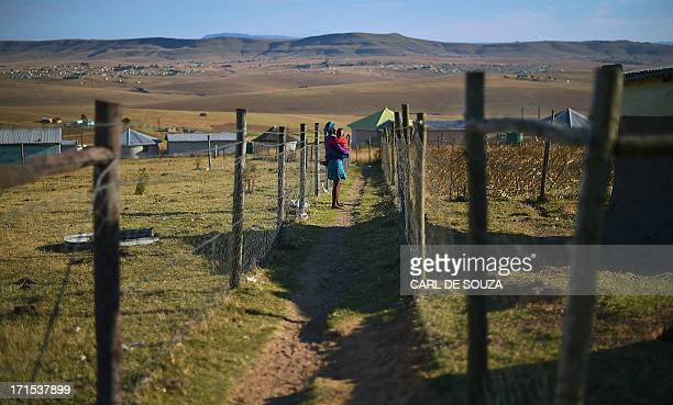 A woman holding her baby is pictured on June 26 2013 in Qunu a rural village where former South African President Nelson Mandela grew up Mandela's...