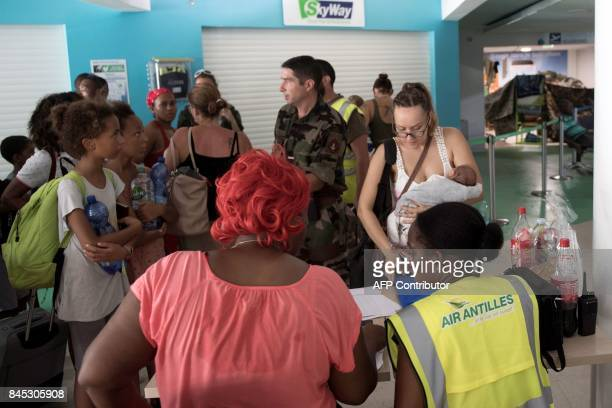 A woman holding her baby registers to board a plane at GrandCase Esperance airport to leave SaintMartin on September 10 2017 on the French Carribean...