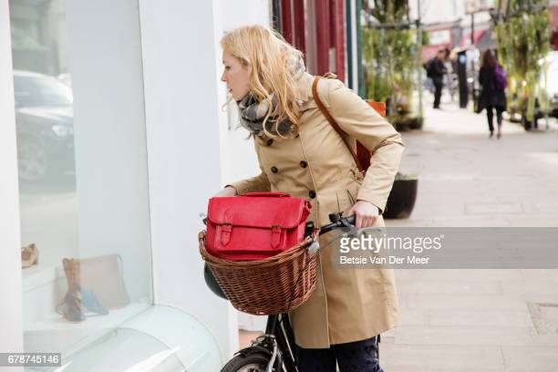 Woman holding her bicycle, looks at shoe display in shop window.