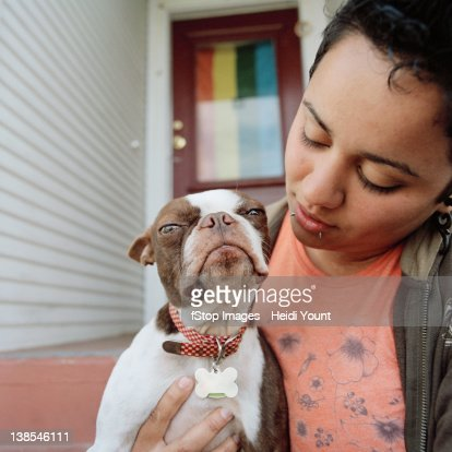 A woman holding her dog : Stock Photo