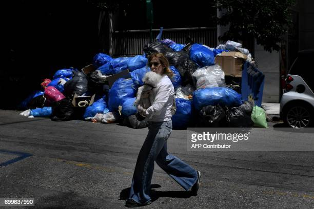 TOPSHOT A woman holding her dog walks past a pile of garbage in central Athens on June 22 as contract garbage collectors refuse for the third day to...