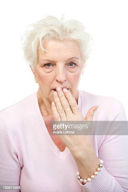 Woman holding her hand in horror in front of her mouth