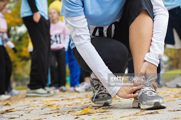 Woman holding her hurt ankle at a race