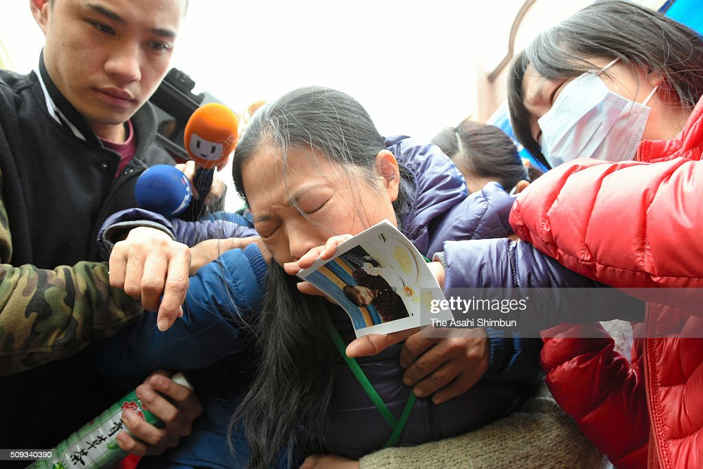 A woman holding her missing son's portrait sheds tears in front of the collapsed building on February 10, 2016 in Tainan, Taiwan. A strong magnitude 6.4 earthquake hit Southern Taiwan on February 6, killing at least 46 people and 94 unaccounted for.