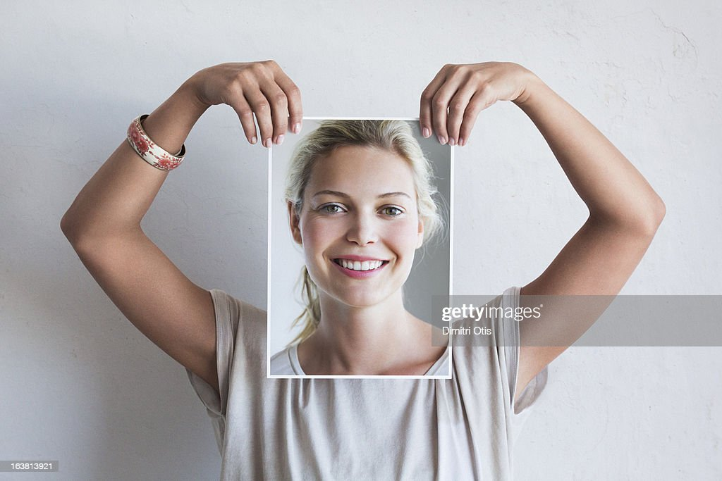 Woman holding her portrait in front of her face : Stock Photo