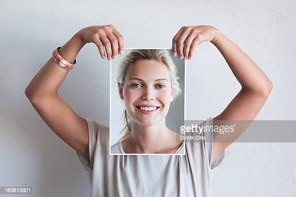Woman holding her portrait in front of her face