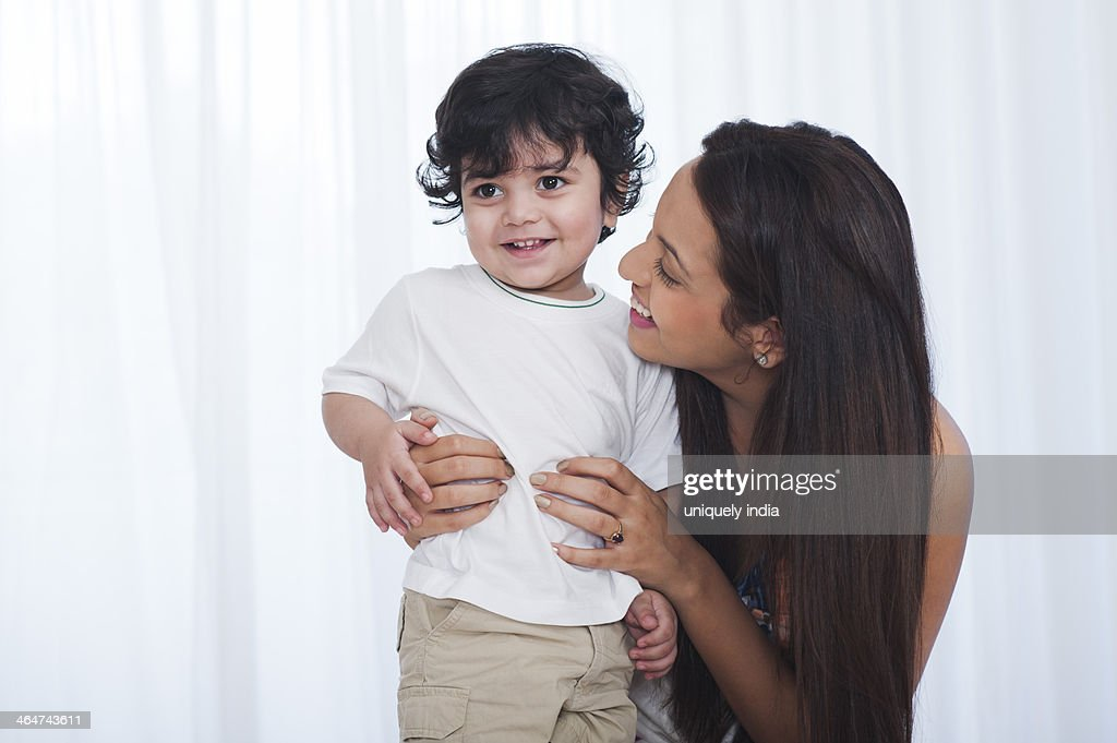 Woman holding her son and smiling : Stock Photo