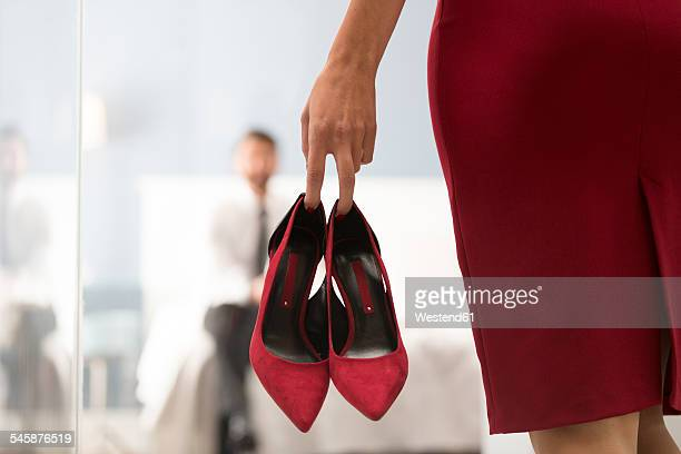 Woman holding high heels with man in bedroom