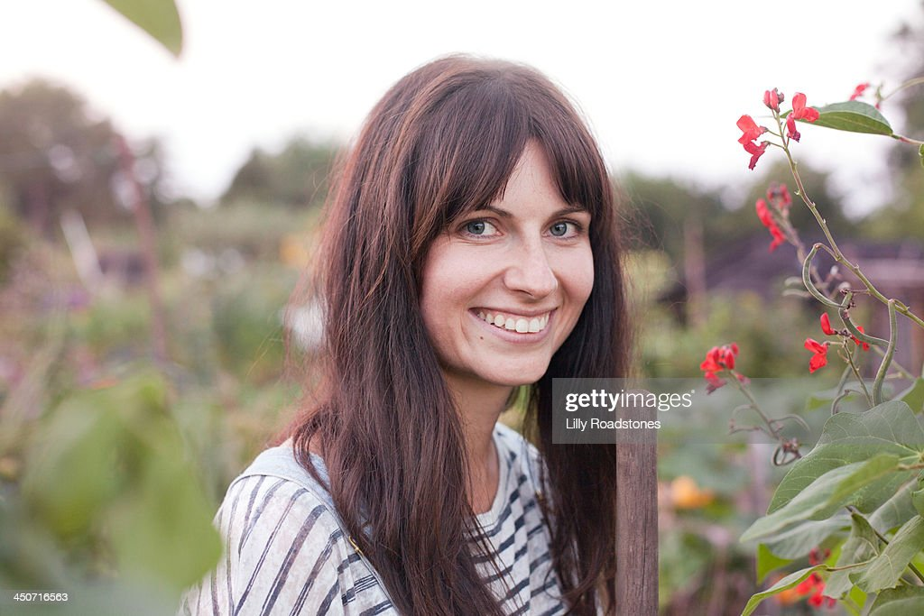 Woman holding hoe and smiling at allotment : Stock Photo