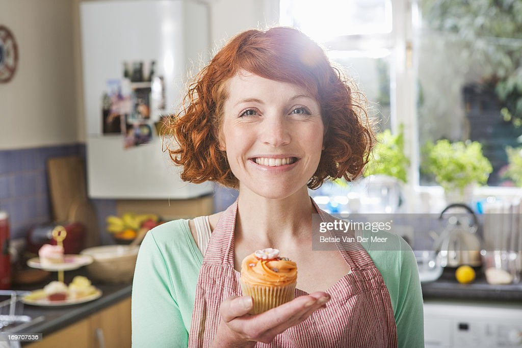 Woman holding homemade cupcake smiling. : Stock Photo